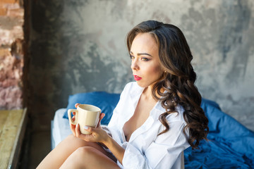 young beautiful girl in a white shirt sits on a bed drinking coffee in an apartment loft