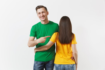 European young brunette woman, smiling man showing thumbs up, football fans in yellow green empty t-shirt isolated on white background. Sport play soccer cheer fan people lifestyle concept. Back view.