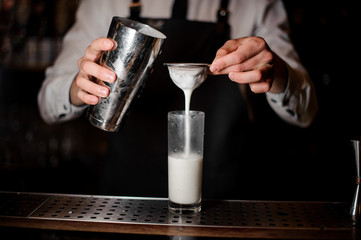 Bartender adding the alcoholic drink from the steel shaker