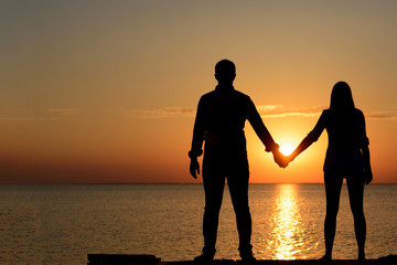 Two lovers (teenagers) are standing on the bridge (berth) and holding hands looking at the ocean at sunset