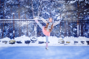 A girl, a figure skater is skating in a park on ice