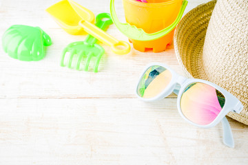 Summer holidays vacation concept background, hat, sunglasses, sand toys, white wooden background copy space