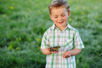 Cute blond little boy with defferent emotions holding little frog at summer day over green background.