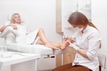 Podiatrist doctor cleaning foot from callus.
