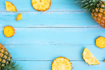 Tropical pineapple on wood plank blue color. frame layout summer vacation background concept..