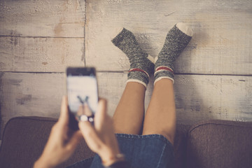young nice caucasian lady on the sofa taking picture with smartphone at her feet with happy and funny socks. home daily scene in fun lifestyle. share life with friends concept
