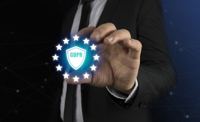 GDPR. Data Protection Regulation. Cyber security and privacy. Businessman holding a shield with a symbol (GDPR)