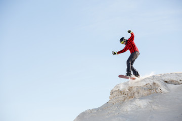 Picture of man with snowboard jumping from snowy mountain slope