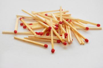 Matches, white wooden thin sticks with red sulfur heads, piled in pile on a white background.