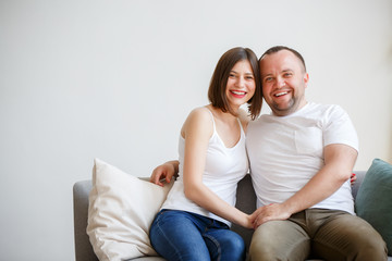 Picture of young married couple sitting on sofa