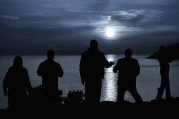 People staring at the moon that shines over the sea