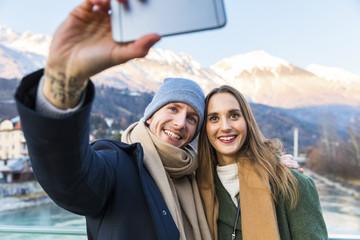 Austria, Innsbruck, portrait of happy young couple taking selfie with smartphone in winter