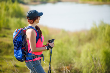 Picture of side view of sporty girl with walking sticks on background of lake and green vegetation