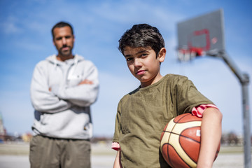 Portrait of boy posing with father on basketball court outdoors