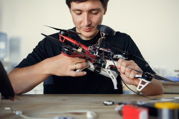Photo of engineer mending square copter at table