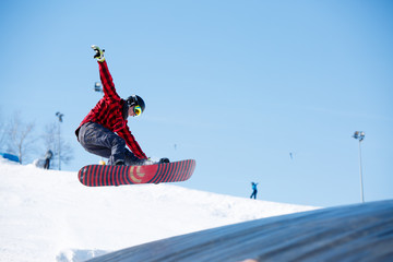 Picture of young sportive man jumping with snowboard