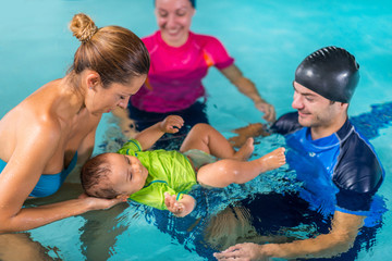 Mother with baby boy and instructors on swimming class