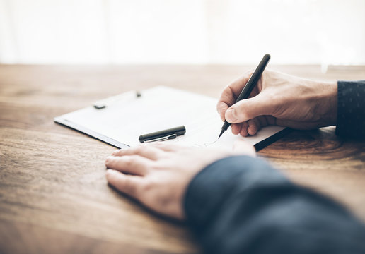 close-up shot of businessman signing contract or document on wooden desk