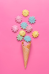 Ice cream cone with pink,blue, yellow meringues on a  colorful  background. Sweet summer concept. Top view. Flat lay.Pastel colors.Dessert