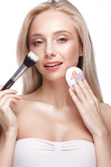 Beautiful young girl with a light natural make-up,brushes for cosmetics and nude manicure. Beauty face. Picture taken in the studio on a white background.