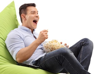 Young guy seated on a beanbag having popcorn and laughing