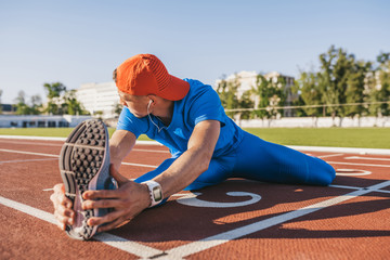 Young athlete male stretching his leg on a track in stadium, preparing for running and jogging workout. Caucasian man exercising outdoors wearing blue sportswear. Sport, people, lifestyle