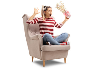 Terrified young woman with a box of popcorn sitting in an armchair