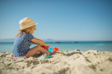 Little girl play on sandy beach with toys, holiday background