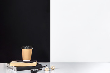 Book, notebook and cup of coffee, black and white wall.