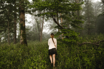 a woman walking through the woods in the morning