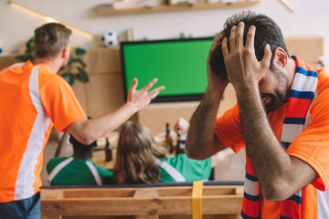 frustrated young man in orange t-shirt and scarf holding hands on head while his friends watching soccer match on tv screen at home