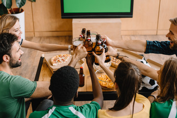 high angle view of football fans celebrating victory and clinking beer bottles and glasses over table with pizza, popcorn and chips at home
