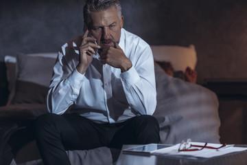 Tired businessman talking on phone