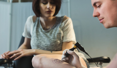 Professional tattoo artist making tattoo on leg