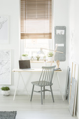 Grey wooden chair standing by the desk with lamp and laptop with empty screen in white room interior with window and fresh plants