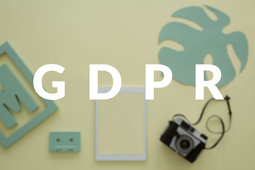 GDPR in a creative business concept. Blurred photo of a photographer's desk with a tablet and a vintage camera. White banner in the front