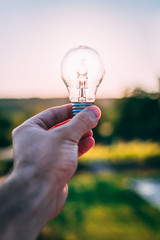 Bulb in a hand in front of the sun symbolizing an energy going from the sun