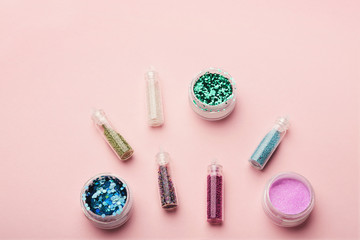 Assortment of glitters for nail design on pink background, top view
