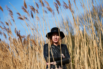 Cool woman wearing felt hat standing among reeds, portrait