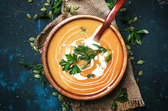 Creamy pumpkin soup with herbs and seeds in wooden bowl, rustic style, black background, top view