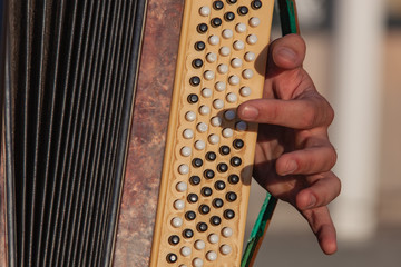 Close-up of a hand of the musician playing on keys of an old accordion