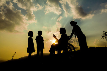 silhouettes of happy family playing together on the mountain at sunset