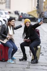 Ragazze in viaggio sorridendo indicando