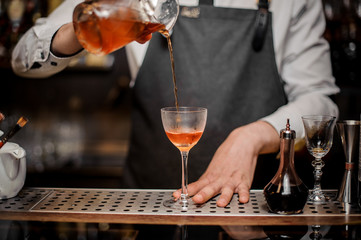 Bartender pourring an alcoholic drink into the cocktail glass