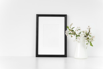 Black A4 passepartout frame mock up with spring cherry bouquet. Mock up for your photo, design or text.
