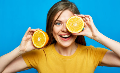 Close up face portrait of smiling woman holding two orange slice