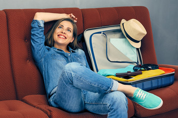 Happy woman sitting with travel suitcase on sofa.