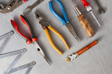 Set of different construction vintage tools and instruments for household on gray concrete background
