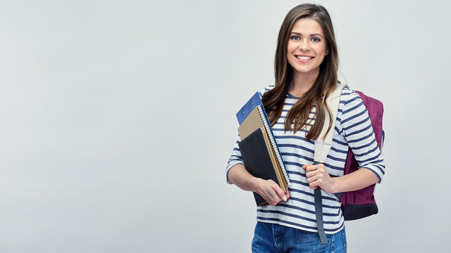 Student woman with backpack holding book and notebooks.