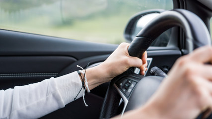 the man holds his hands on the steering wheel, drives the car
